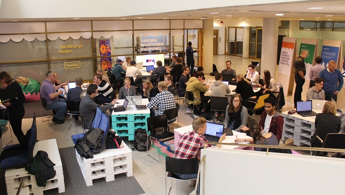 Metropolian opiskeilijoita istumassa pienissä pöytäryhmissä Helsingin kaupungintalon ala-aulassa.