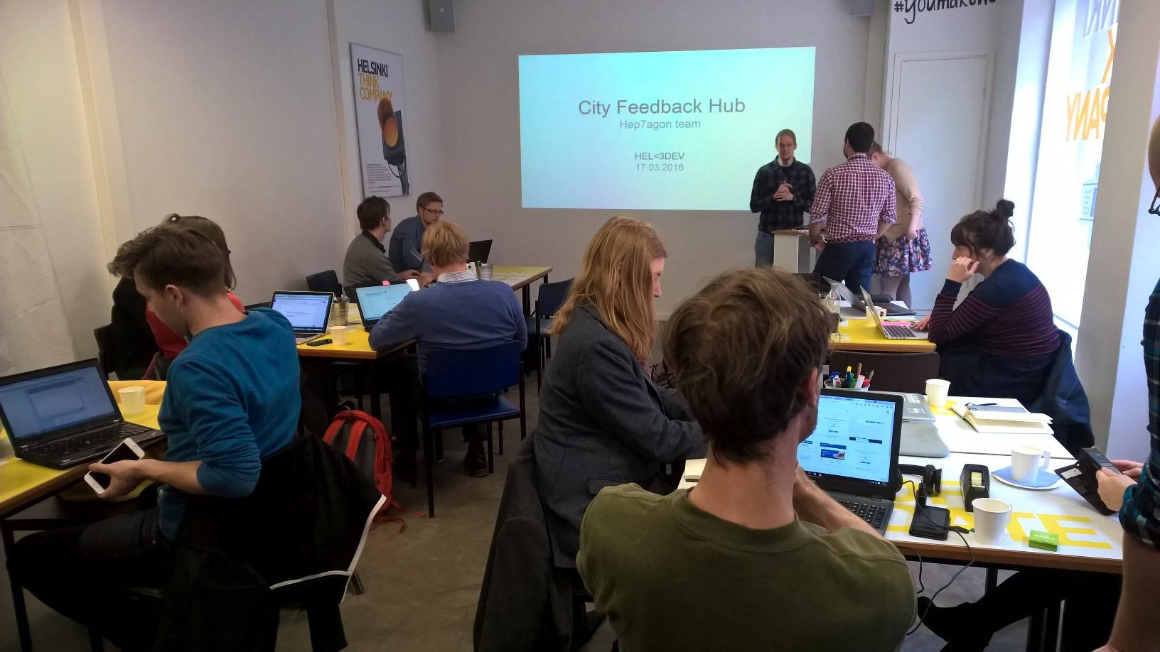 Ihmisiä pöytien ääressä työpajailemassa Helsinki Loves Developers -kehittäjätapaamisessa.