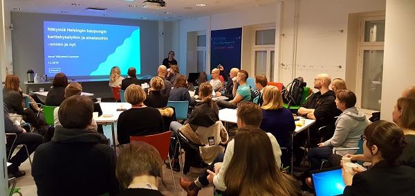 Valokuva Väliniemi-Laursonista puhumassa istuvien katsojien edessä.