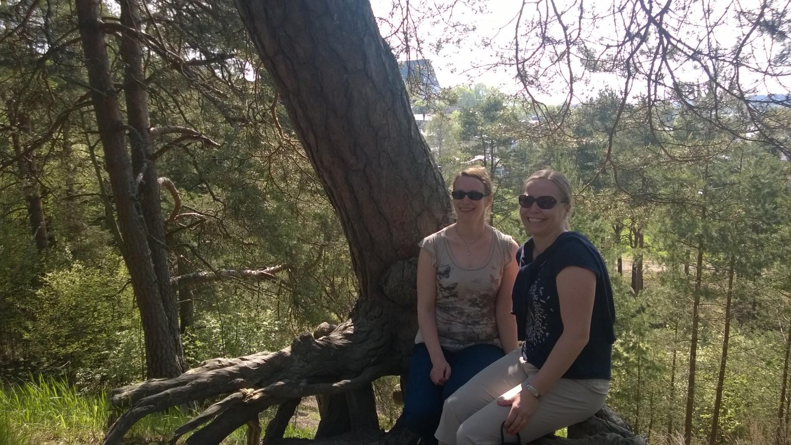 Hami Kekkonen ja Tanja Lahti istumassa suuren männyn juurakolla kauniina kevätpäivänä Porvoossa.