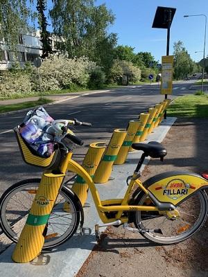Yksi telineeseen pysäköity keltainen kaupunkipyörä.