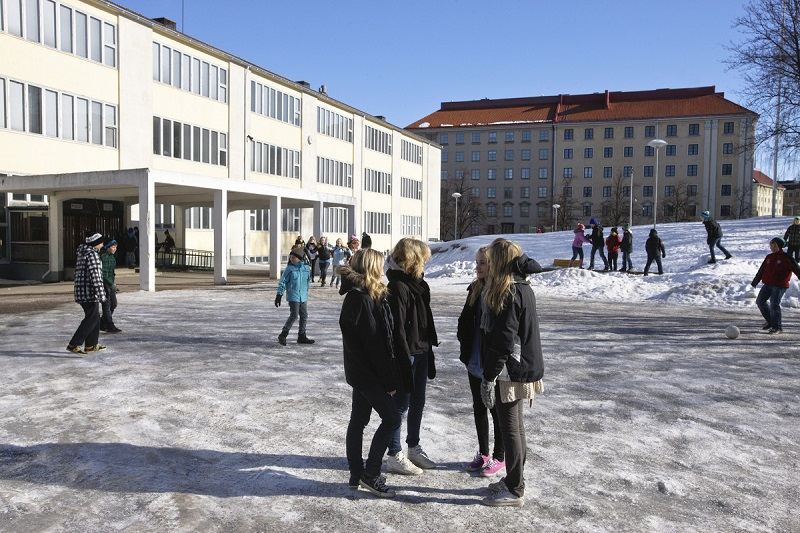 Lapsia viettämässä välituntia lumisella koulun pihalla.