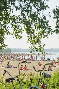 Ihmisiä aurinkoisella uimarannalla.