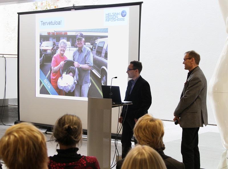 Valokuva Ville Melonista ja Pekka Vuoresta Helsingin kaupungintalon aulassa esittelemässä HRI-palvelua kuulijoille diaesityksen avulla.