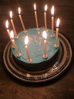 Valokuva HRI-synttärikakusta, jonka päällä on kymmenen sytytettyä kynttilää.