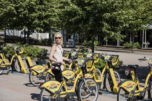 Valokuva naisesta ottamassa telineestä kaupunkipyörää.