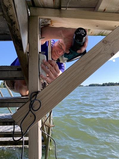Valokuva Aapo Ristasta asentamassa laituriin uimaveden lämpötilaa mittaavaa sensoria.
